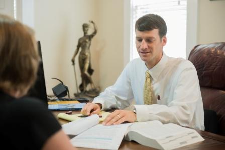 Travis Studdard meets with a client about her workers' compensation case