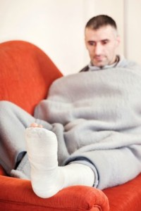 Many with leg injury rests leg on sofa arm
