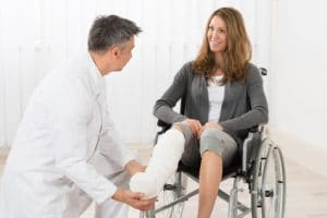 Doctor therapist examining leg of patient in cast and wheelchair