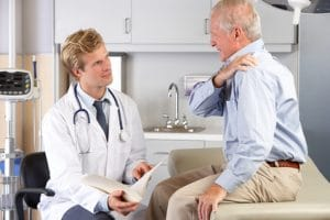 Doctor examining man with shoulder pain