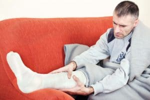 Man with broken leg ankle or foot sitting on sofa