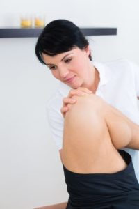 Physical therapist does exercises with patients leg and knee