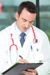 Male doctor writing a prescription or an order for a test or a referral