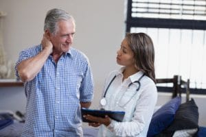 Senior man suffering from neck pain speaking with female doctor or therapist