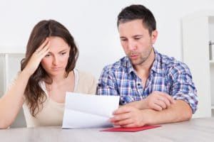 Man and woman reading letter and looking confused