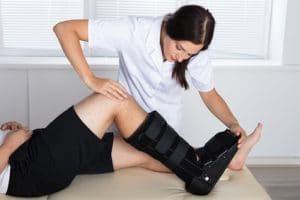 Nurse adjusting walking brace for patient with foot or ankle injury