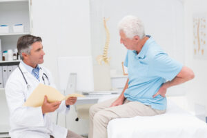 Male patient suffering from back pain speaks with doctor
