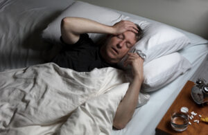 Man with headache trying to fall asleep in bed with medication on nightstand