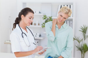 Doctor examining patient with neck pain
