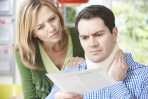 A husband and wife read a letter concerning the scheduling of a functional capacity evaluation for the husband's neck injury