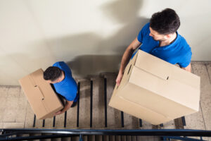 Two men carrying cardboard boxes down stairs