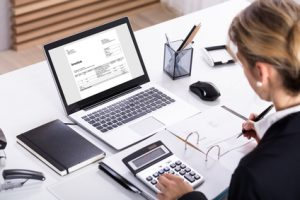Businesswoman in office using calculator and laptop