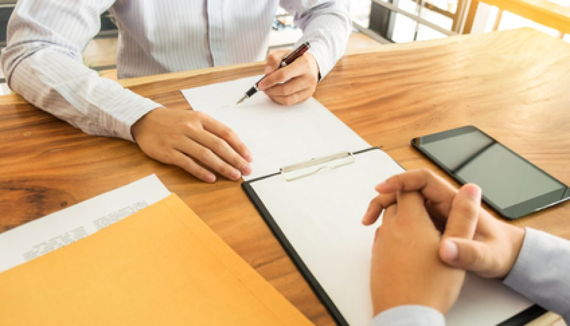 People work on documents at a table in an office