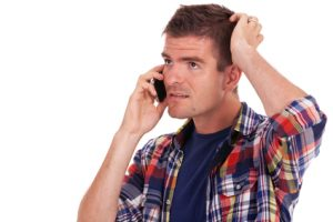 Confused man talking on cell phone