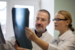Male and femal doctor examining x ray images