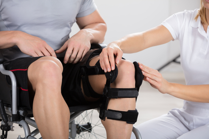 Doctor examines knee brace of patient who has suffered an injury at work