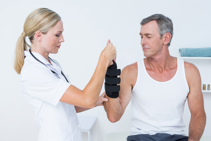 Doctor examines wrist of man who developed carpal tunnel syndrome from repetitive work