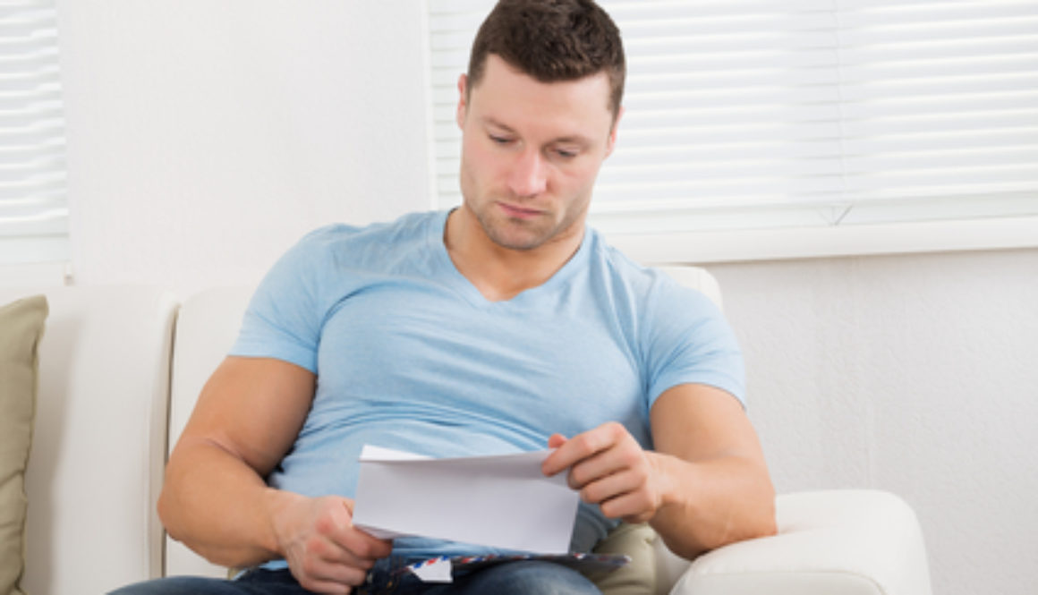 A man sitting on a couch review a letter about his workers compensation settlement
