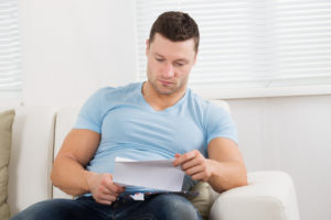 Man reading letter on couch