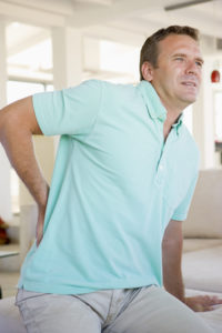 Man with back pain from workers compensation injury sits down