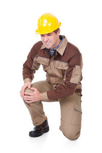 A man in a hardhat has sharp pain in his knee as he stands up while at work