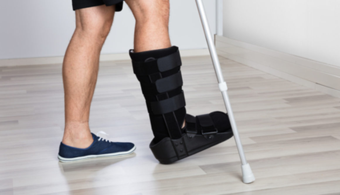 Injured worker walking with a cane in a walking boot