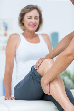 Doctor examining womans knee